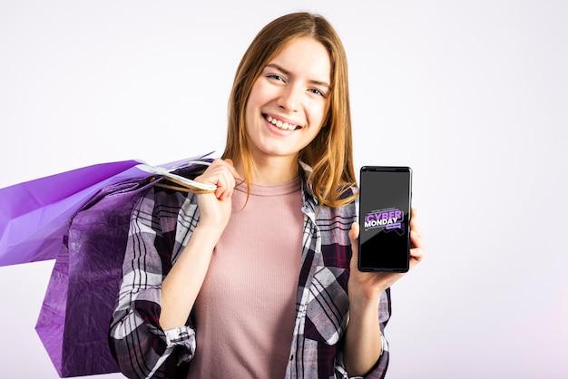 Frau, die papiertüten trägt und einen telefonspott hochhält