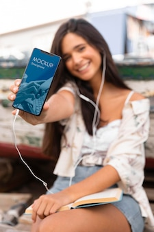 Frau, die smartphone hält und musik auf kopfhörern hört