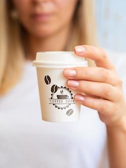 Frau, die von einer kaffeepapiertasse trinken will