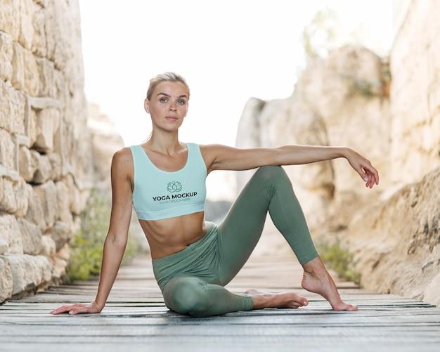 Frau, die yoga macht, während sie einen modell-sport-bh trägt