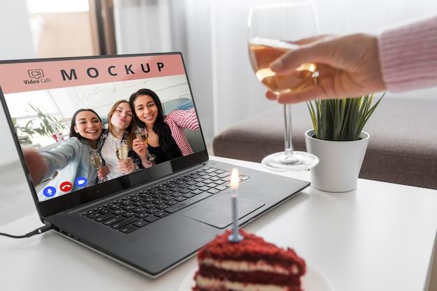 Frau, die zu hause mit freunden über laptop und getränk feiert
