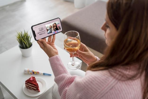 Frau, die zu hause mit freunden über smartphone und getränk feiert