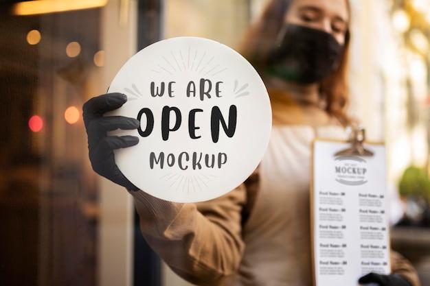 Frau hält ein restaurant wir sind offenes zeichen