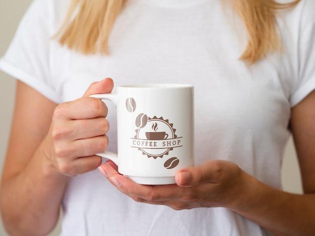Frau hält eine kaffeetasse hoch