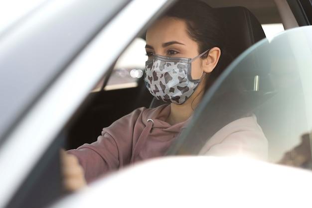 Frau im auto, das maske trägt