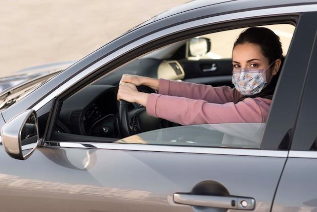 Frau im auto, die medizinische maske trägt
