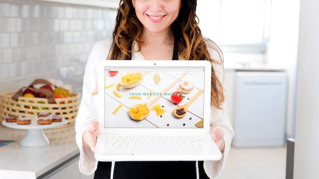 Frau in der küche, die laptopmodell darstellt