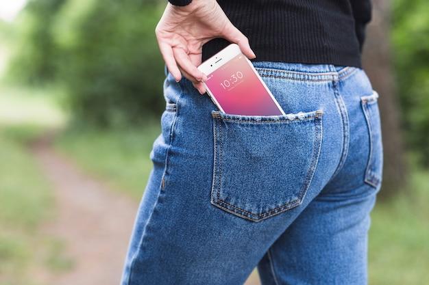 Frau in der natur mit smartphone in der tasche