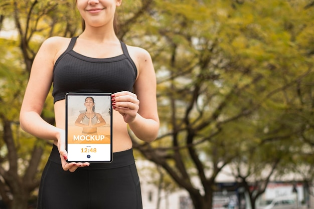 Frau in der sportkleidung, die digitales tablettenmodell hält