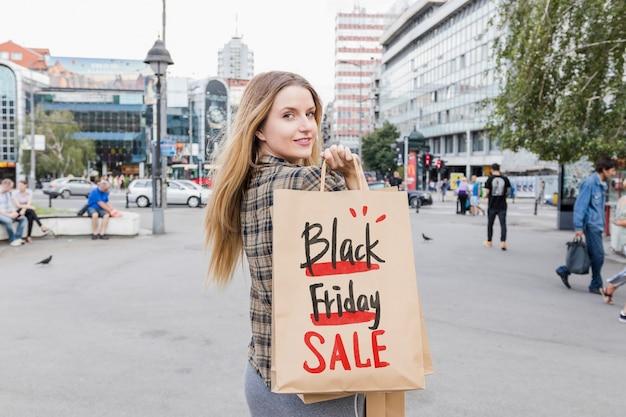 Frau in der stadt mit schwarzen freitag-taschen