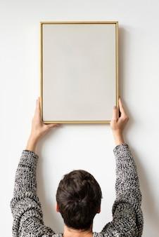 Frau in einem schwarzen pullover, der einen holzrahmen an einem weißen wandmodell hängt