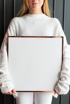 Frau in einem weißen pullover mit einem holzrahmenmodell