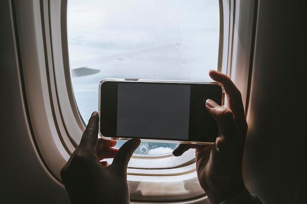 Frau macht ein foto vom fensterplatz in einem flugzeug