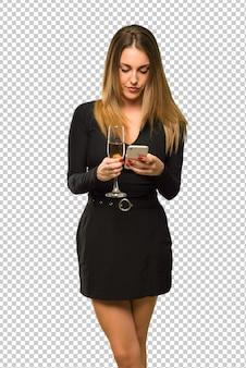 Frau mit dem champagner, der das neue jahr 2019 feiert, das eine mitteilung oder eine e-mail mit dem mobile sendet