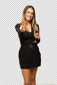 Frau mit dem champagner, der das neue jahr 2019 glücklich feiert und zwei mit den fingern zählt