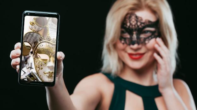 Frau mit der karnevalsmaske, die smartphonemodell zeigt