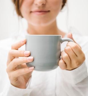 Frau mit einem kaffeetassenmodell