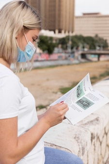 Frau mit maske, die buch auf straße liest