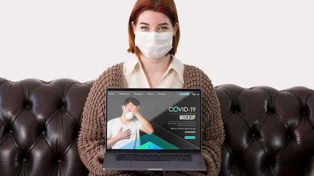 Frau mit masken, die laptop beim sitzen auf der couch halten