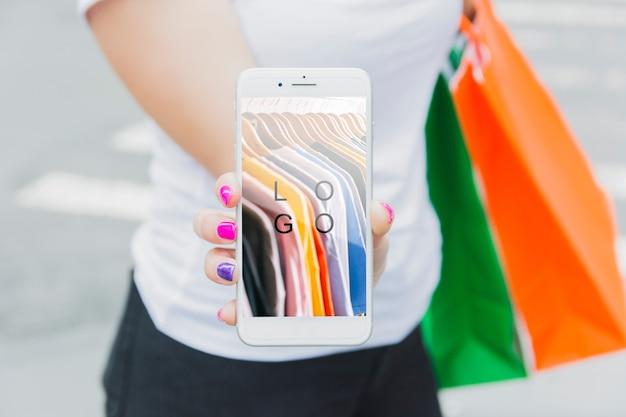 Frau mit smartphone-modell und einkaufstaschen