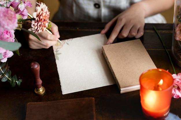 Frau schreibt einen brief auf ein leeres papiermodell