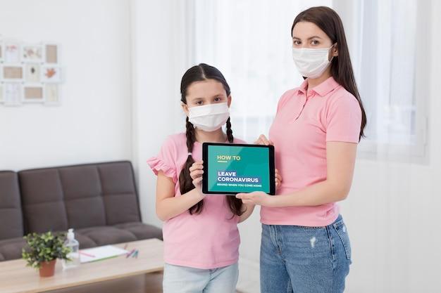 Frau und tochter halten ein tablettenmodell mit covid-19-präsentation