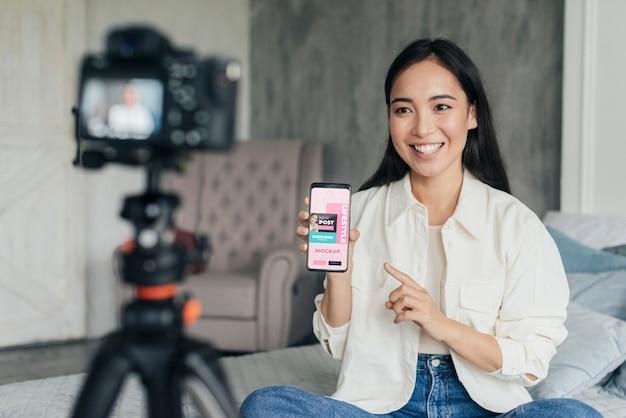 Frau vlogger, die ein telefonmodell hält