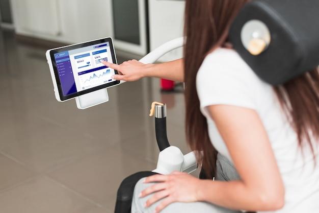 Frau, welche die digitale tablette eines rehabilitationsstuhls verwendet