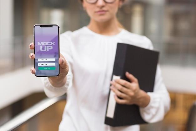 Frau zeigt ihren telefonbildschirm