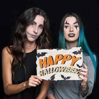 Frauen, die papier mit halloween-beschriftung halten