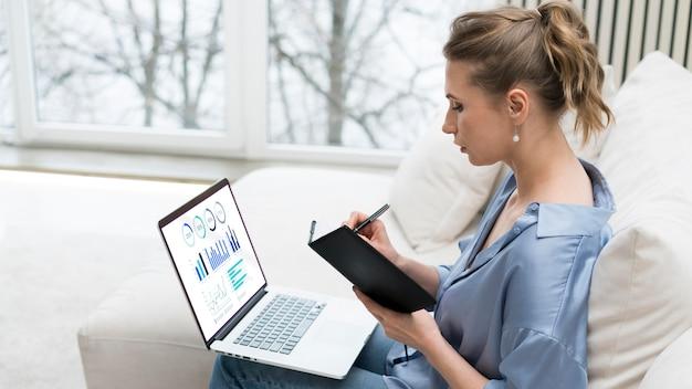 Frauenfernbedienung, die am laptop arbeitet