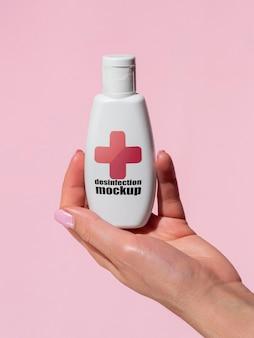 Frauenhand, die desinfektionsflaschenmodell hält
