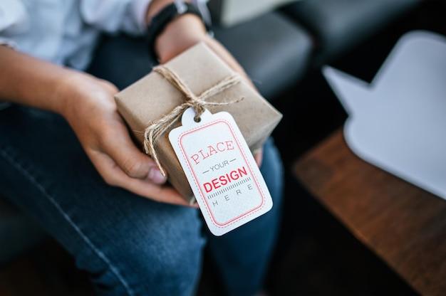 Frauenhand halten geschenkbox mit preisschild psd modell