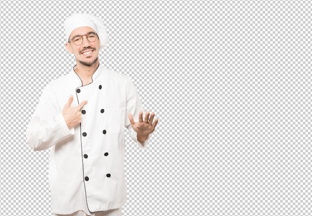 Freundlicher junger koch, der eine geste der ruhe tut
