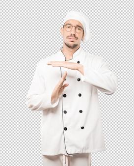 Freundlicher junger koch, der mit seinen händen eine auszeitgeste macht