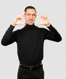 Freundlicher junger mann, der eine geste macht, ein foto mit den händen zu machen