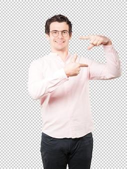 Freundlicher junger mann, der eine geste vom machen eines fotos mit den händen macht
