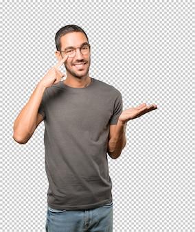 Freundlicher junger mann, der eine geste von vorsichtig sein mit seiner hand zeigt auf sein auge macht