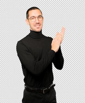 Freundlicher junger mann, der geste applaudiert