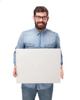 Freundlicher kerl ein leeres plakat zeigt