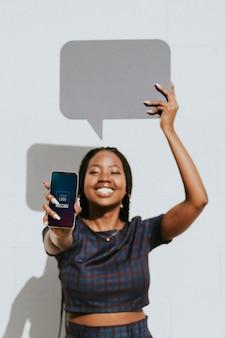 Fröhliche schwarze frau, die eine leere sprechblase mit einem telefonmodell zeigt