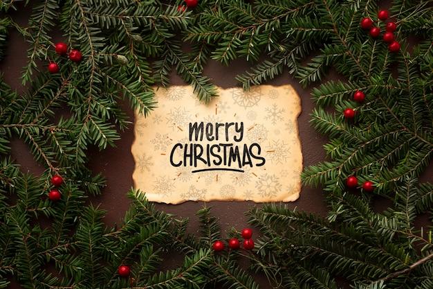 Frohe weihnachten auf blättern eines weinlesepapiers und der weihnachtskiefer