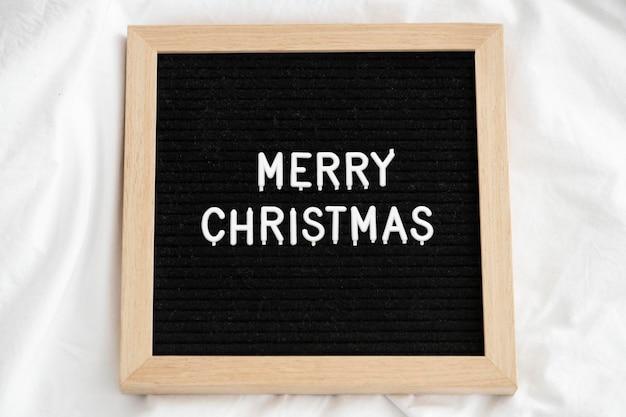 Frohe weihnachten auf einem holzrahmen
