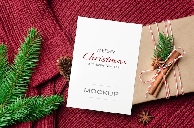 Frohe weihnachten grußkartenmodell mit dekorierter geschenkbox und tannenzweig auf gestricktem hintergrund