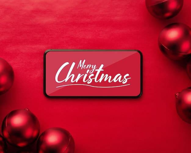 Frohe weihnachten smartphone-modell mit weihnachtskugeln Premium PSD