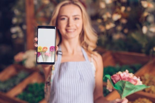 Frühlingskonzept mit der frau, die smartphonemodell hält