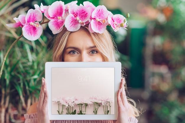 Frühlingskonzept mit der frau, die tablettenmodell hält