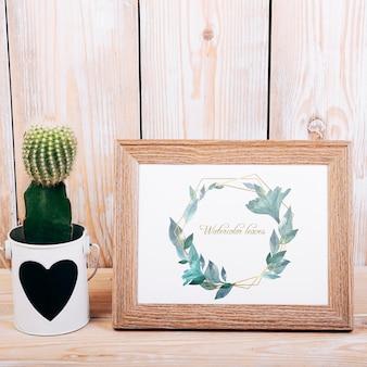 Frühlingsmodell mit holzrahmen und kaktus