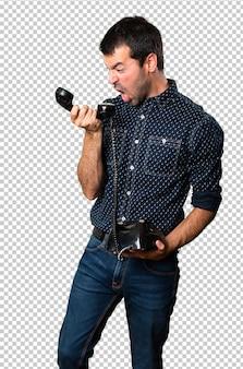 Frustrierter brunettemann, der mit weinlesetelefon spricht