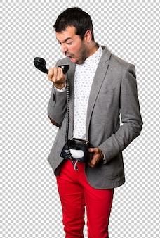 Frustrierter gutaussehender mann, der mit weinlesetelefon spricht